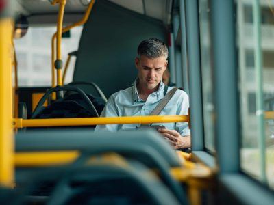 Confident businessman traveling by bus and using a digital tablet